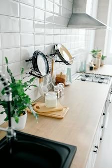 Minimale witte keuken interieur met plant op houten werkbladen.