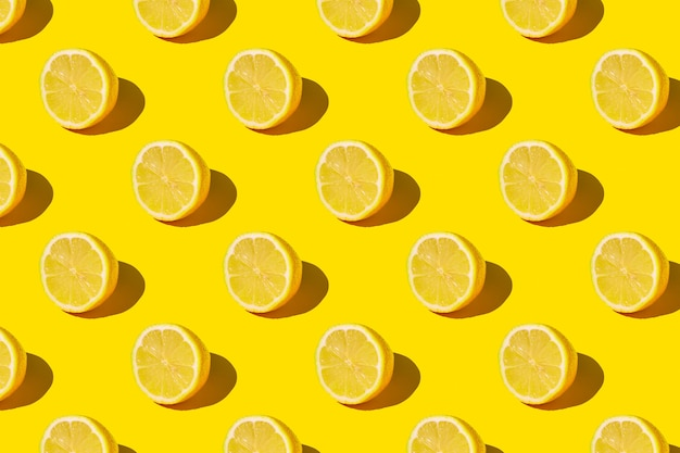 Minimale zonnige zomer plat lag fruit achtergrond. verse citroenplakken op geel patroon als achtergrond.