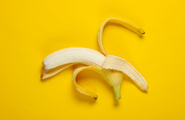Minimalisme fruit concept. geopende rijpe banaan op een gele tafel. bovenaanzicht
