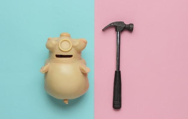 Minimalisme mode-concept spaarvarken met hamer op roze blauwe achtergrond bovenaanzicht