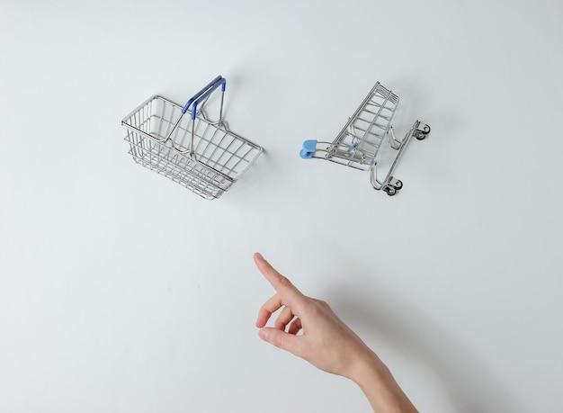 Minimalisme mode-concept vrouwelijke hand kiest tussen winkelwagentje of mand