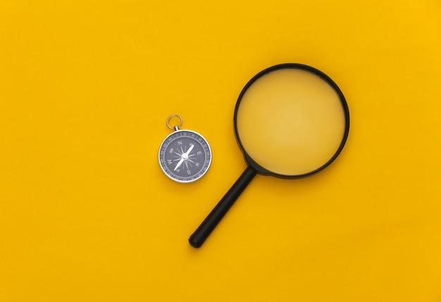 Minimalisme reizen, avontuur plat leggen. kompas en vergrootglas op gele achtergrond. bovenaanzicht