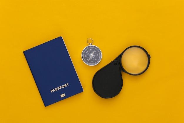 Minimalisme reizen, avontuur plat leggen. kompas en vergrootglas, paspoort op gele achtergrond. bovenaanzicht