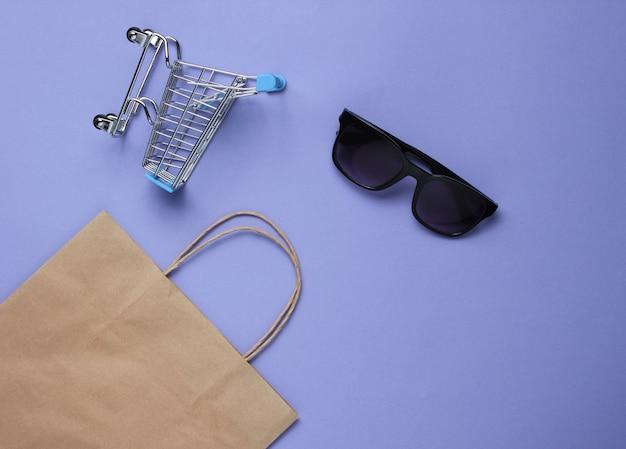 Minimalisme winkelconcept. papieren boodschappentas, mini-winkelwagentje en zonnebril op paarse achtergrond.