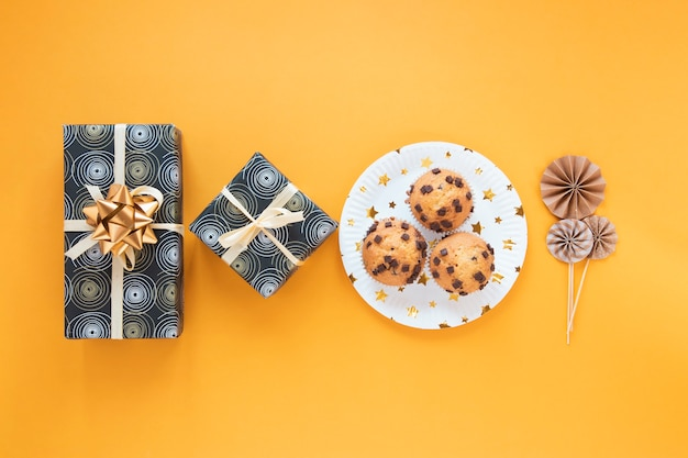 Minimalistisch arrangement met verjaardagscadeautjes en cupcakes