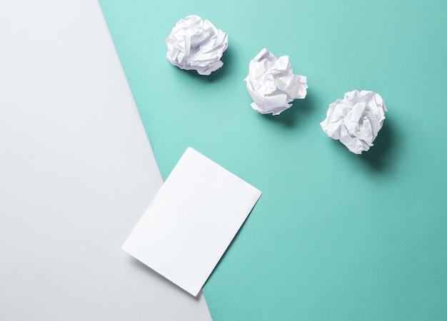 Minimalistisch bedrijfsconcept. verfrommelde papieren ballen en leeg wit blad op grijsblauw