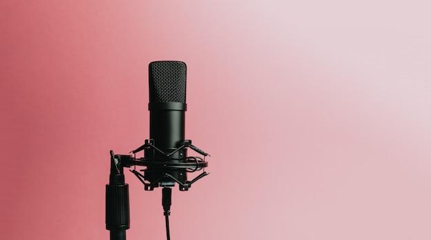 Minimalistisch beeld van een streaming microfoon op een pastelroze achtergrond met kopie ruimte, minimaal concept