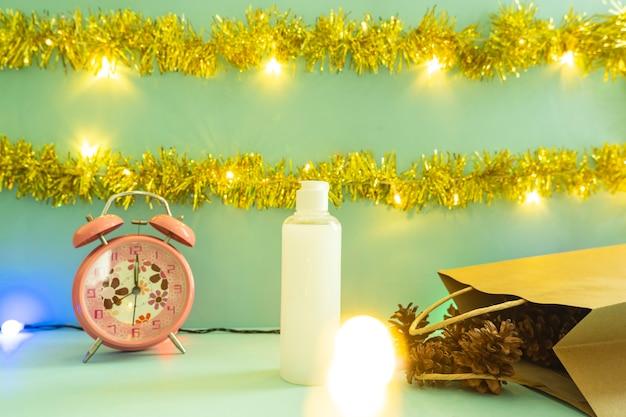 Minimalistisch conceptidee dat producten weergeeft. cosmetische flessen op kerstmis en nieuwjaar achtergrond. wekker. pijnboom bloem
