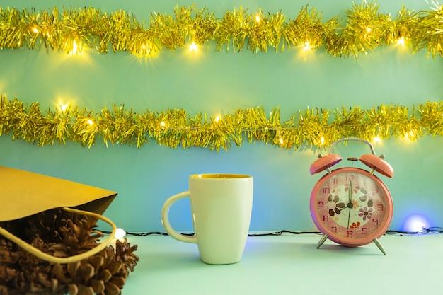 Minimalistisch conceptidee dat producten weergeeft. koffiemok op kerstmis en nieuwjaar achtergrond. wekker. pijnboom bloem