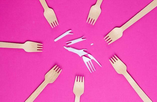 Minimalistisch ecologisch schoon stilleven. pop-art. gebroken plastic vork onder vele houten vorken op roze achtergrond. bestek gemaakt van natuurlijke materialen