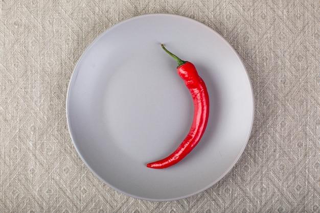 Minimalistisch grijs bord met chili rode peper op linnen tafelkleed