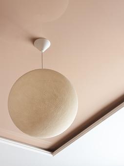 Minimalistisch interieur met plafondlamp in de vorm van een rieten bol.