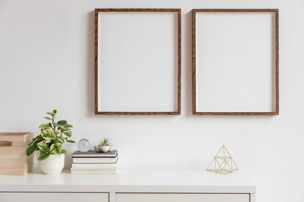 Minimalistisch interieur van interieur met twee bruine houten mock-up fotolijsten op de witte plank met boeken, mooie plant in stijlvolle pot en woonaccessoires. witte muur.