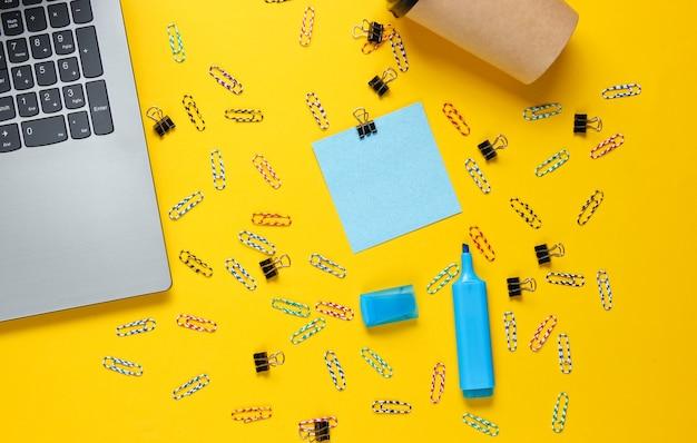 Minimalistisch kantoorstilleven. laptop, briefpapier, koffiekopje op gele achtergrond.