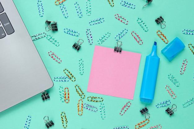 Minimalistisch kantoorstilleven. laptop, briefpapier op blauwe achtergrond.