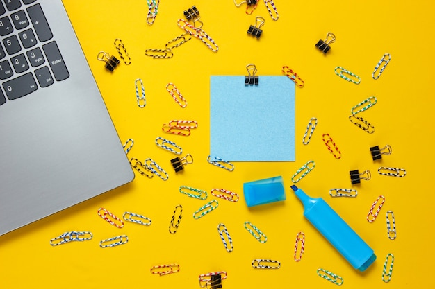 Minimalistisch kantoorstilleven. laptop, briefpapier op gele achtergrond.