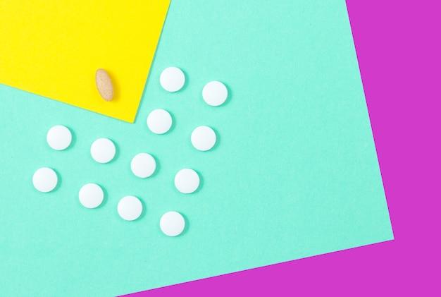 Minimalistisch medisch concept. een groep identieke witte tabletten en één unieke tablet op een pastelkleurige achtergrond. bovenaanzicht