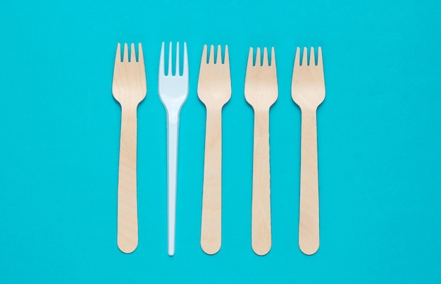 Minimalistisch milieuconcept. houten en plastic vorken op een roze blauwe achtergrond. creatieve eco achtergrond. bovenaanzicht