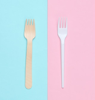 Minimalistisch milieuconcept. houten en plastic vorken op een roze blauwe pastel achtergrond. creatieve eco achtergrond