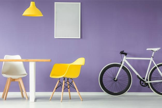 Minimalistisch modern interieur met een witte en gele stoel een fiets een lege tafel en een hangende?