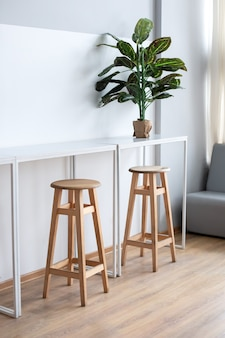 Minimalistisch ontwerp met tafel en hoge barkrukken voor coffeeshop. interieur van werkruimte in coworking voor freelancer
