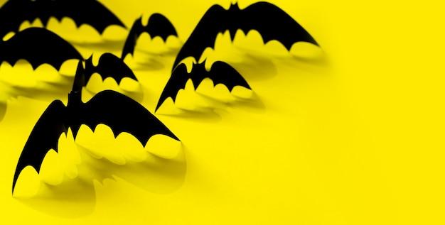 Minimalistisch papier vleermuispatroon met vallende schaduw op geel.