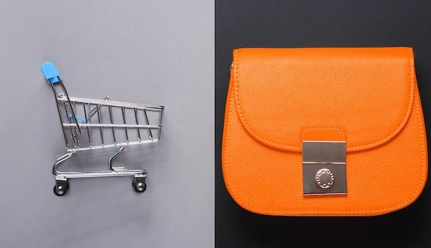 Minimalistisch shopaholic concept. gele lederen tas, mini winkelwagentje op een papieren achtergrond. bovenaanzicht