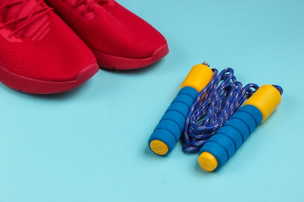 Minimalistisch sportstilleven. sportkleding. rode sportschoenen voor training en springtouw op blauwe achtergrond.
