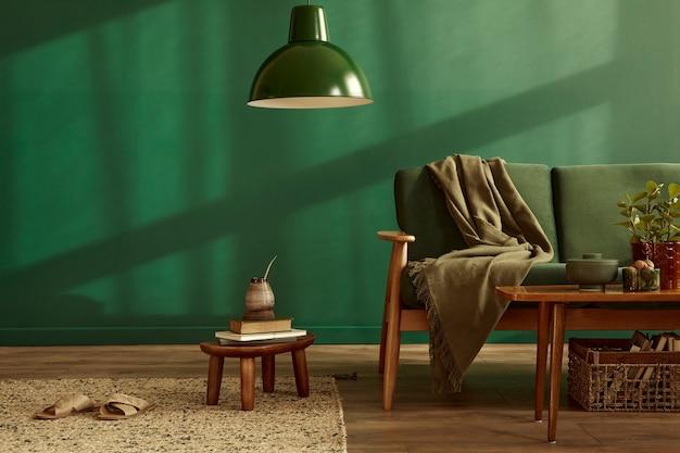 Minimalistisch woonkamerinterieur in stijlvol huis met design fluwelen bank, tapijt op de vloer, bruin houten meubilair, plant, boek, hanglamp
