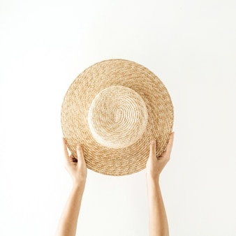 Minimalistisch zomer- en reisconcept. vrouw handen met een strooien gele hoed