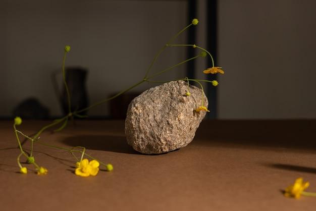 Minimalistische beigebruine stillevencompositie met natuurmateriaalsteen en gele bloemabstract...