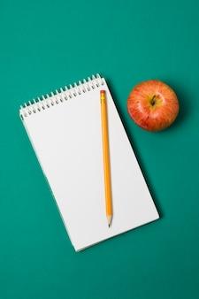 Minimalistische bovenaanzicht apple en bureau benodigdheden