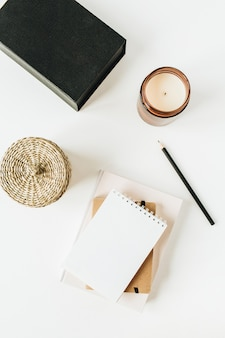 Minimalistische bureauwerkruimte met notitieboekje op wit.