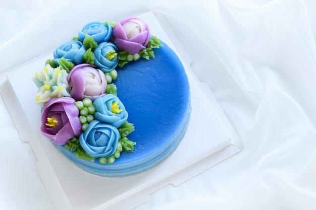 Minimalistische cake gemaakt van pandan layer sweet cake en versierd met schattige bloemen op een witte doek.