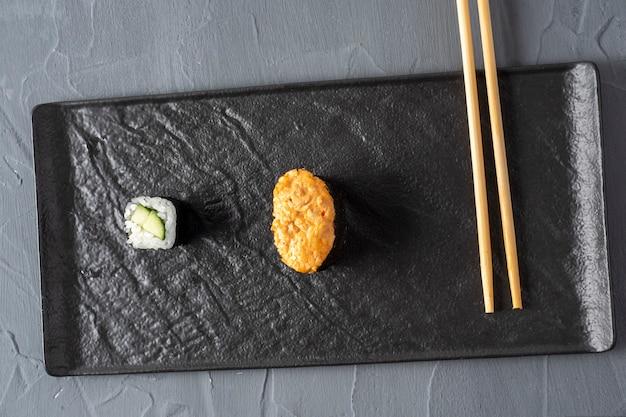 Minimalistische compositie. broodje, gunkan en bamboestokken op een getextureerde donkere plaat. bovenaanzicht, plat gelegd