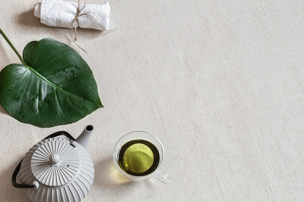 Minimalistische compositie met groene thee in een kopje, theepot en badaccessoires. gezondheid en schoonheid concept.