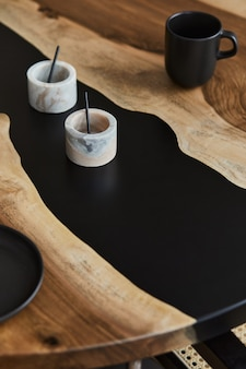Minimalistische compositie op de design houten en epoxy tafel met zwarte kopjes en lepel, marmeren vat. moderne eetkamer interieur. details..