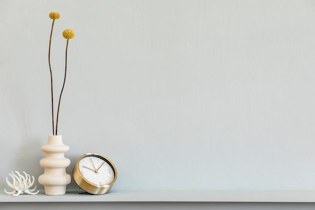 Minimalistische compositie op de plank met gedroogde bloem in designvaas, gouden klok en decoratie op het stijlvolle woonkamerinterieur. grijze muur. ruimte kopiëren.