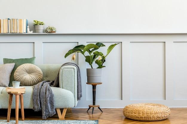 Minimalistische compositie van woonkamer met design bank, salontafel, plant, boeken, decoratie, kussens, plaid, tapijt, houten lambrisering en elegante persoonlijke accessoires in stijlvol interieur.
