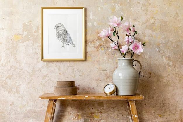 Minimalistische compositie van woonkamerinterieur met gouden frame, houten bankje, gouden klok, magnolia in vaas en elegante persoonlijke accessoires in modern interieur.