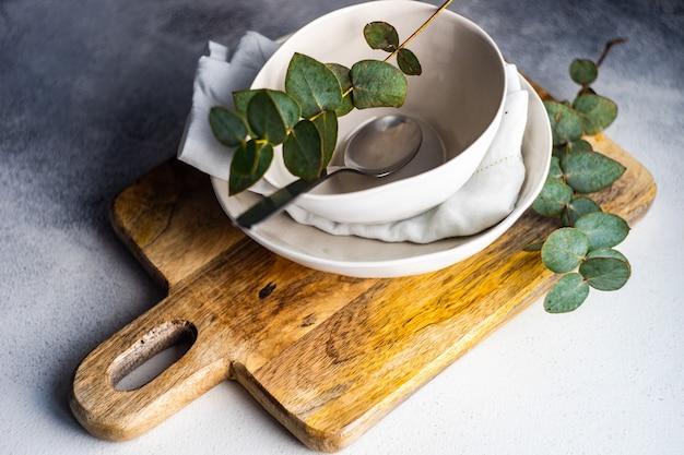 Minimalistische couvert met verse eucalyptusbladeren op betonnen tafel