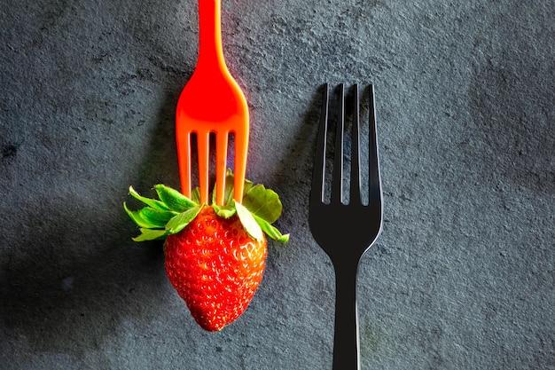 Minimalistische elegante, zwarte vork en een aardbei op zwarte tafel