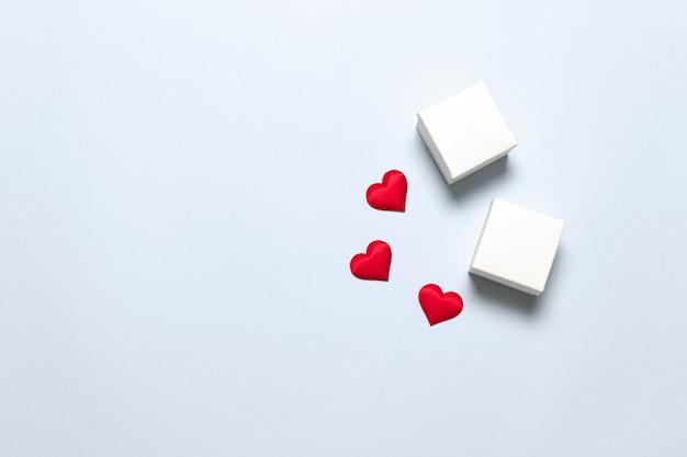 Minimalistische feestelijke compositie met witte lege verrassingsdozen en hartvorm op een licht