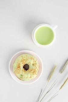 Minimalistische flatlay met kopje groene matcha-thee, pistache-donut en driewielige rogge