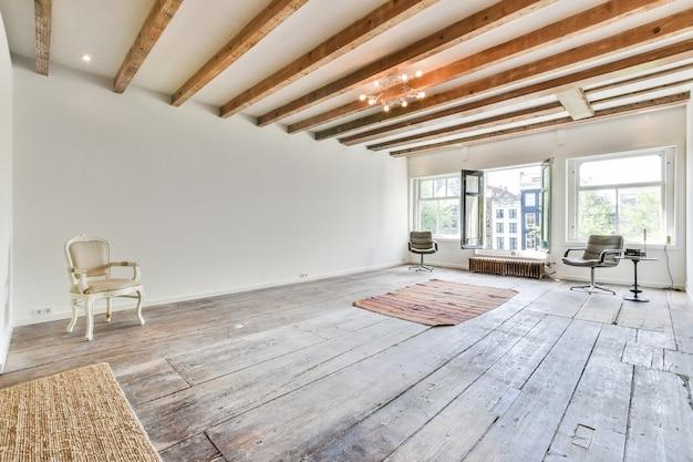 Minimalistische inrichting van lichte huiskamer met houten vloer met stoelen en vloerkleden onder het plafond met houten balken