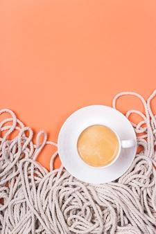 Minimalistische katoenen witte touwachtergrond met kop cappuccino op een koraal gekleurde achtergrond.