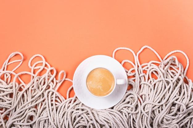 Minimalistische katoenen witte touwachtergrond met kop cappuccino