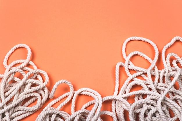Minimalistische katoenen witte touwachtergrond met textuur en contrast op heldere koraalachtergrond.