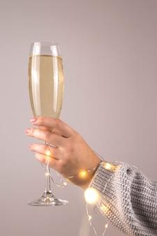 Minimalistische kerst concept van champagne in een vrouwelijke hand.