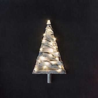 Minimalistische kerstboom met lampjes op een donkere achtergrond. nieuwjaar aard minimaal concept.